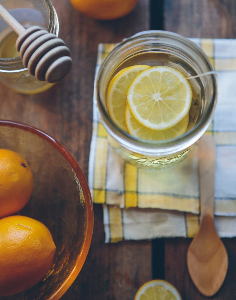 sliced lemons in mason jar filled with water next to bowl of oranges and  glass of honey